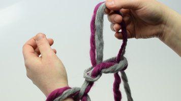 Die Masche, die über die Hand gezogen wird, loslassen. Die aus dem Arbeitsfaden entstandene Schlinge greifen und hochziehen.