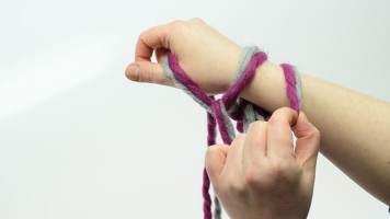 Damit die vordere Masche nicht zu locker gerät, kann der Arbeitsfaden zunächst mit der rechten Hand zwischen Zeigefinger und Daumen gehalten werden. Nun die hintere Masche greifen …