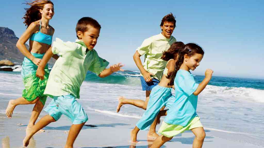 Man running on beach with family.