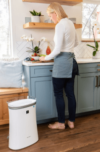 Woman cooking in a kitchen next to Sharp Air Purifier