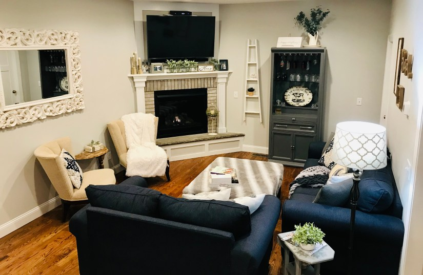 Modern farmhouse living room with navy furniture, light gray walls, white farmhouse ladder on wall, whitewashed brick fireplace, faux fur blankets and navy and gray pillows.