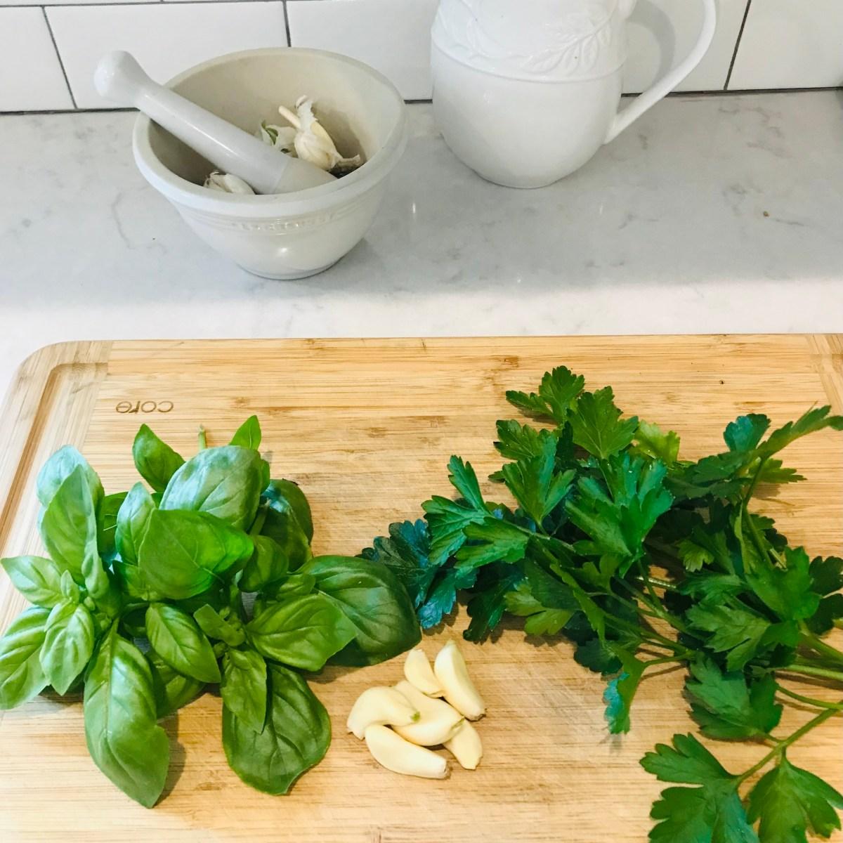 cutting board with fresh basil, parsley and garlic on top