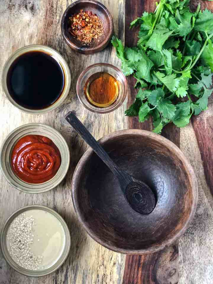 small bowls of ingredients for dan dan sauce on a serving board.