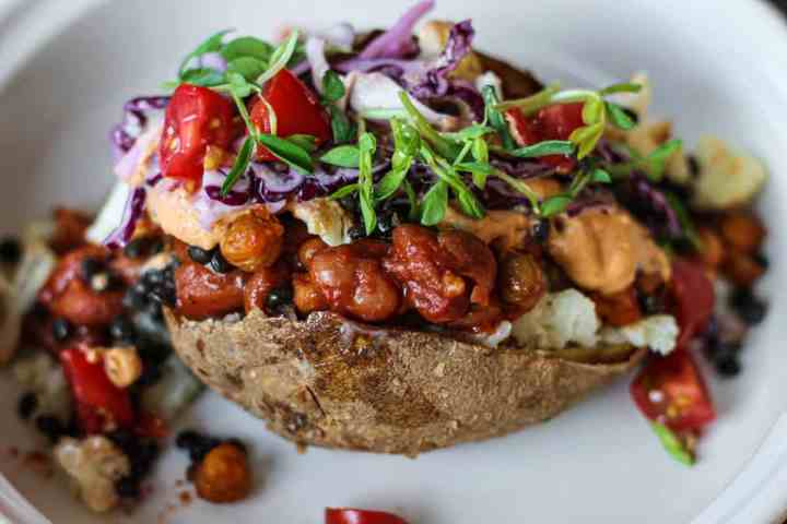 Stuffed baked potato with beans, tomatoes, greens, cole slaw and cashew cream served in a bowl.