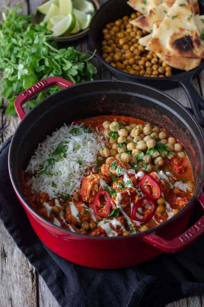 creamy cauliflower and tofu curry in a red dutch oven with chickpeas and naan on the side