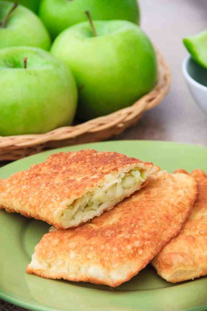 close up image of homemade fried apple turnovers on a green plate with granny smith apples in the background