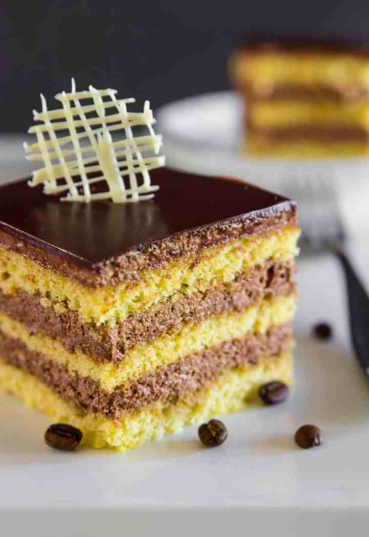a close up image of a homemade opera cake sliced into a square with coffee beans beside it and a fork behind it