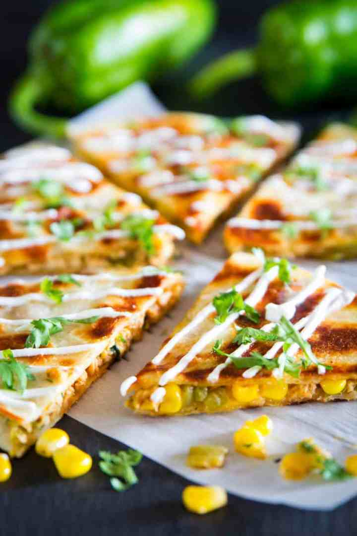 a close up shot of sliced chicken quesadilla with a corn, sour cream, and chopped cilantro on top