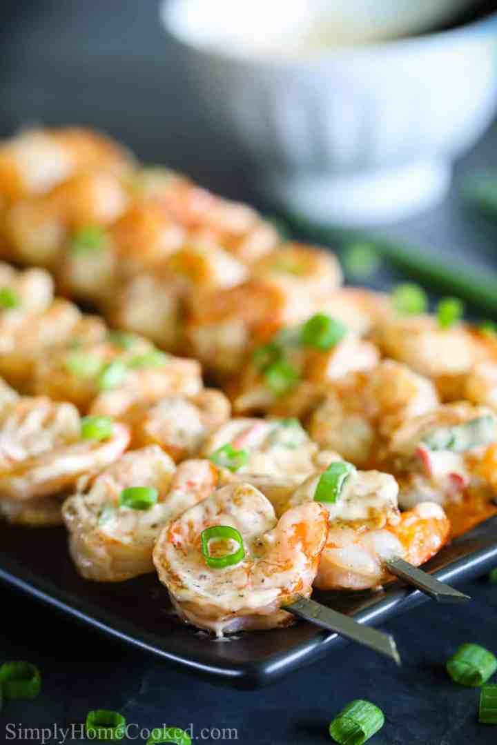 close up image of grilled bang bang shrimp on metal skewers