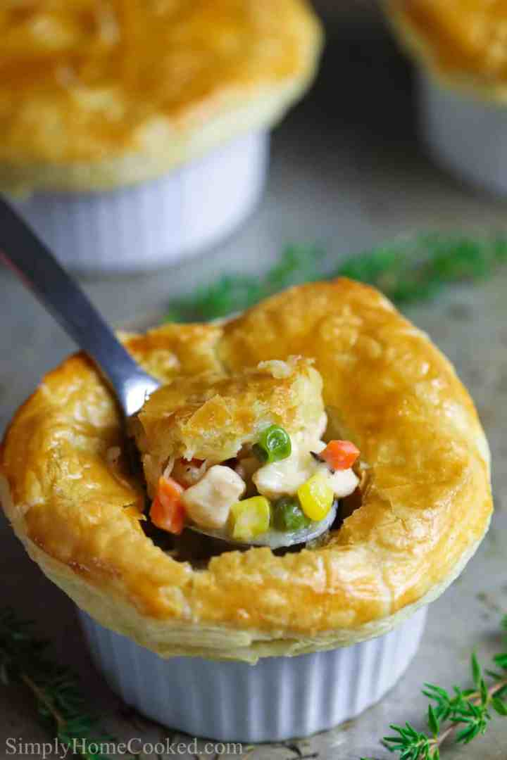 close up image of a mini chicken pot pie with a puff pastry crust and a spoon breaking the center of it