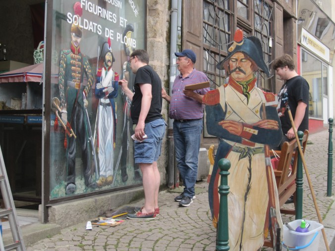 2 people painting a window with old military figurines