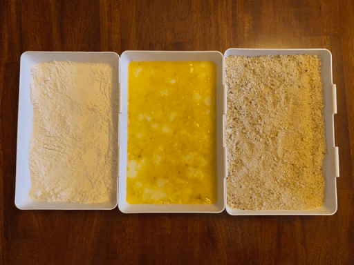 In my first coating tray on the left, I have flour. The next is for eggs, and the last is my bread crumbs. I always make sure to add salt and pepper to each ingredient.