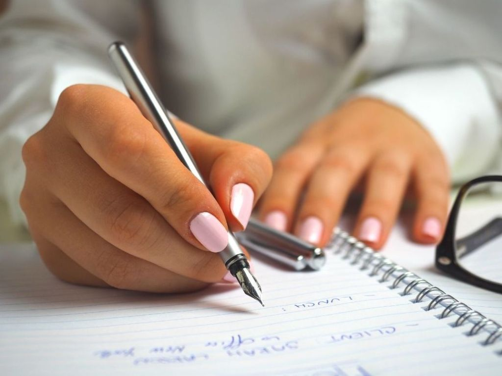 Girl writing a college grocery list