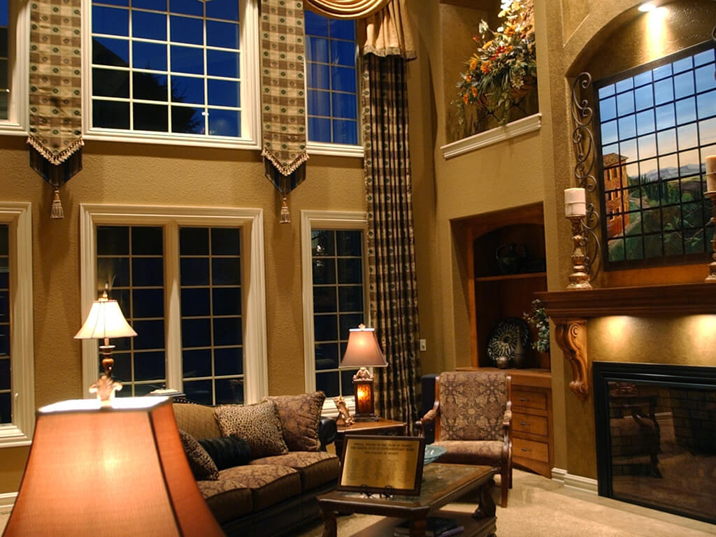 This is a living room with high ceilings and a fireplace.