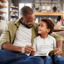 black father reading to son