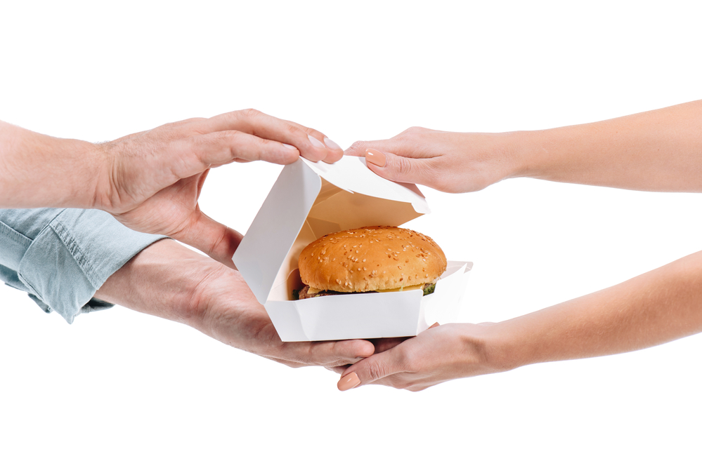 Burger in a box between passed between two people