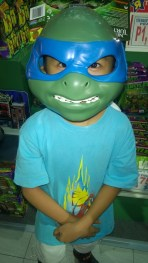 Asher trying on a Leonardo mask on sale.