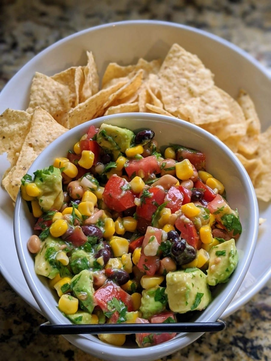 Finished avocado and black bean salad in a white bowl with chips