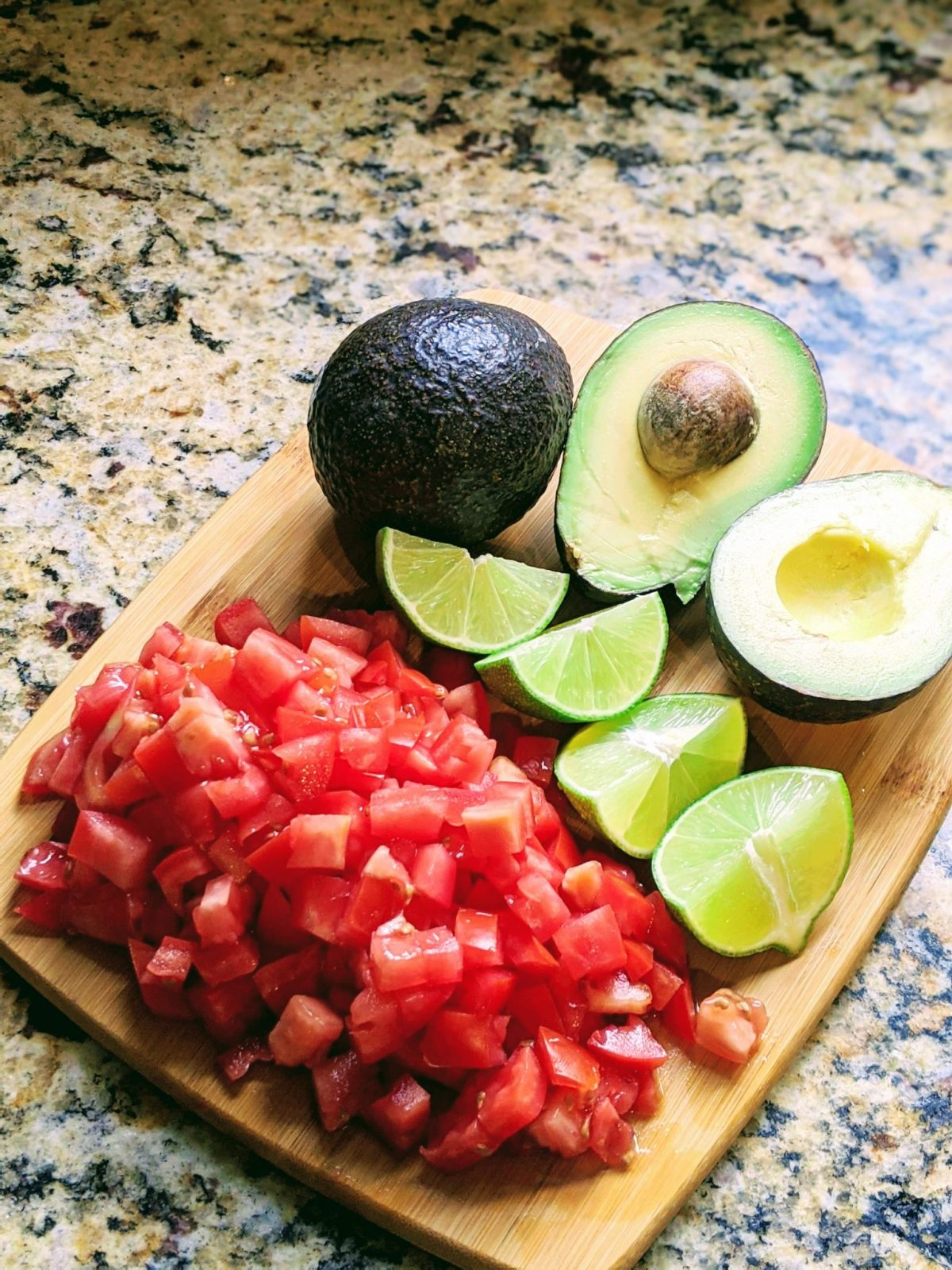 Cutting board with cut tomatoes, sliced limes, and sliced avocados