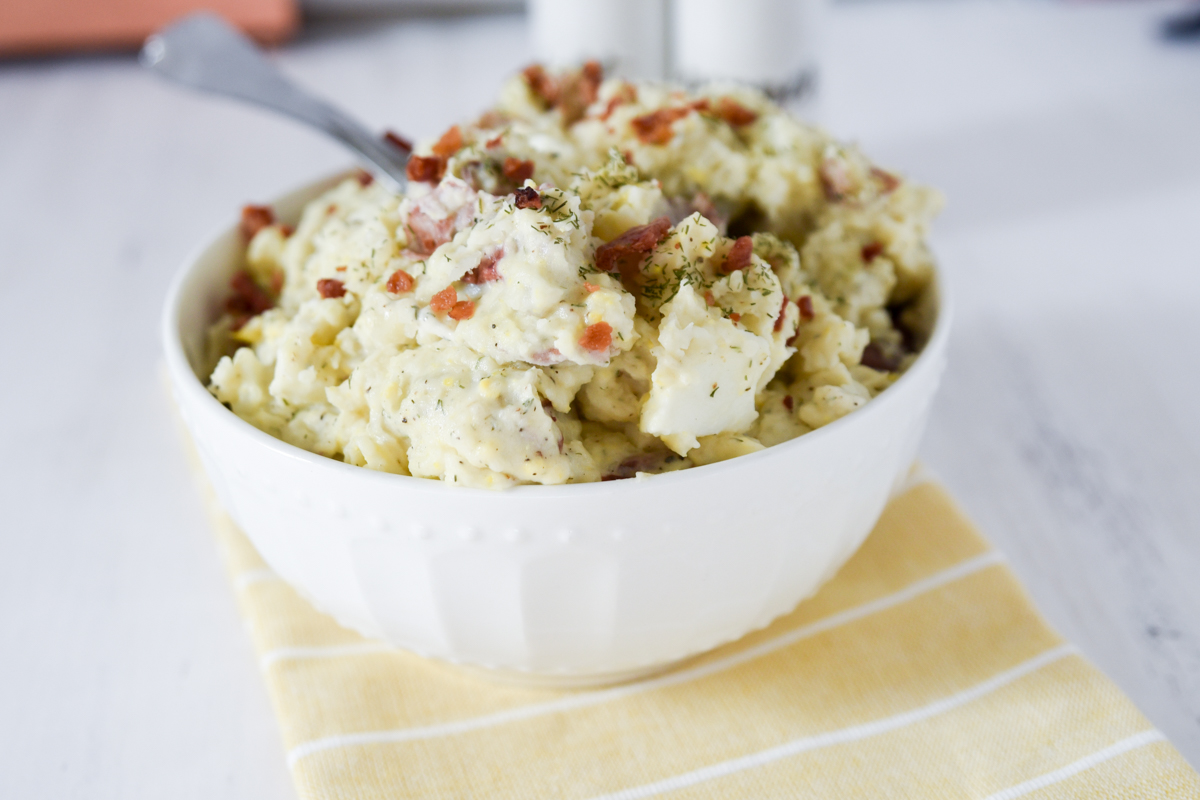 Red Potato Salad in white bowl with spoon.