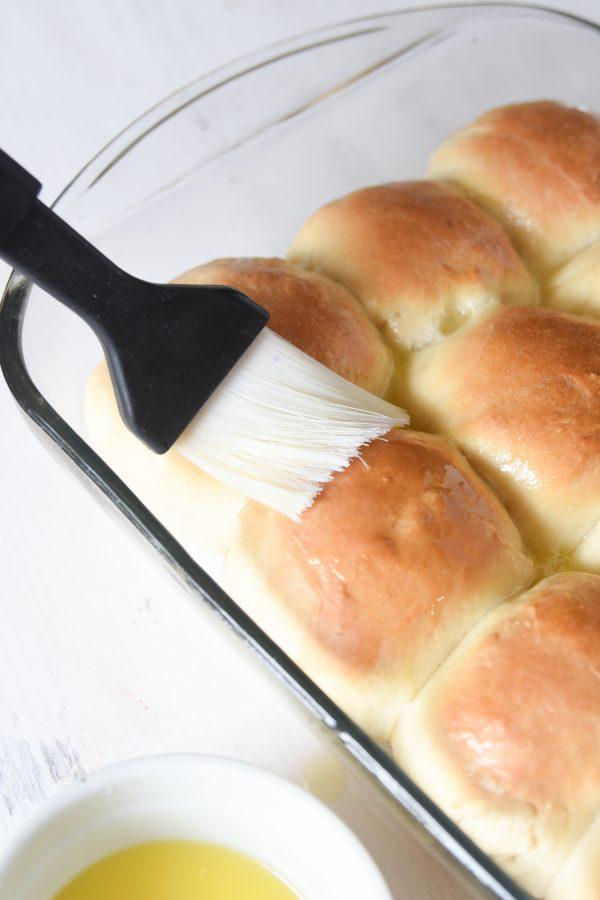 brushing butter on sourdough rolls