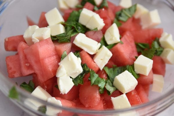 mixing together watermelon salad
