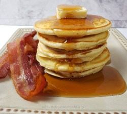 A stack of fluffy buttermilk pancakes topped with a pat of butter, with syrup poured over them and a side of crispy bacon on a white plate