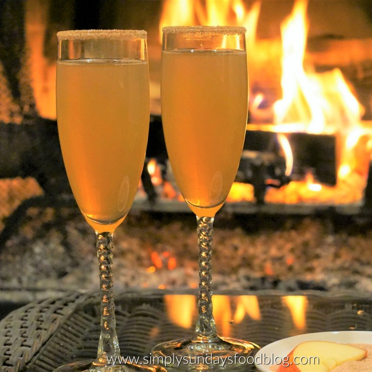 2 champagne glasses with apple cider mimosas on a table with a small bowl of cinnamon sugar and a blazing fireplace in the background