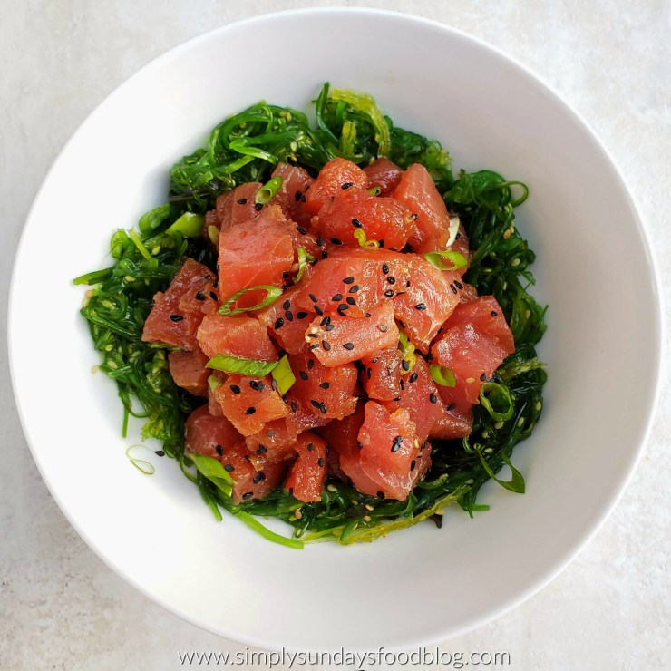 A bowl of tuna poke over a bed of seaweed salad in a large white bowl