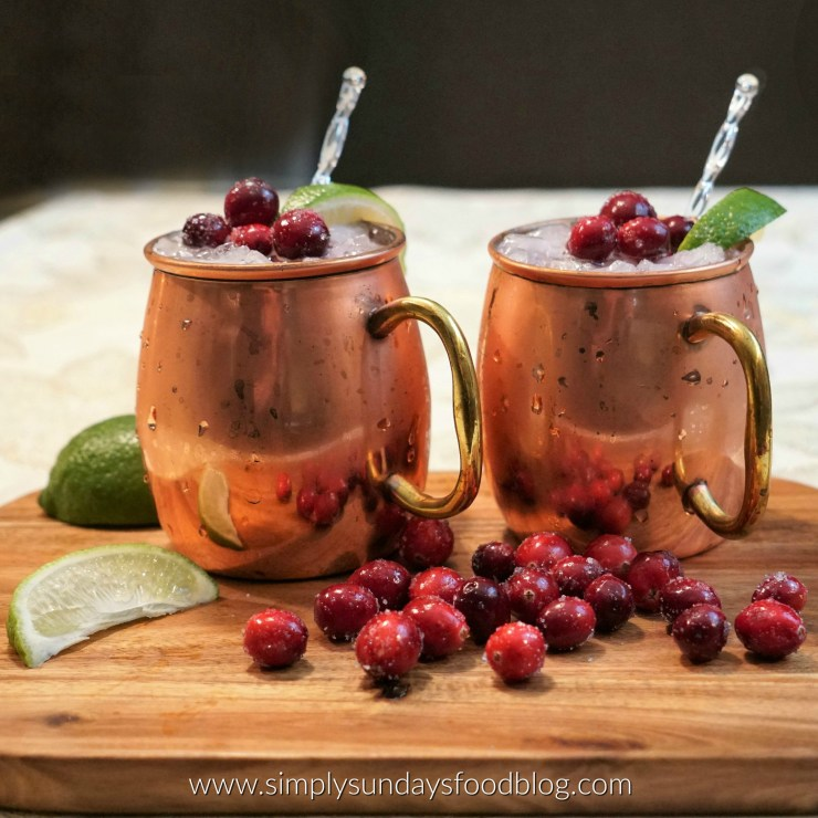 Two copper mugs of cranberry moscow mules on a board with fresh cranberries and limes