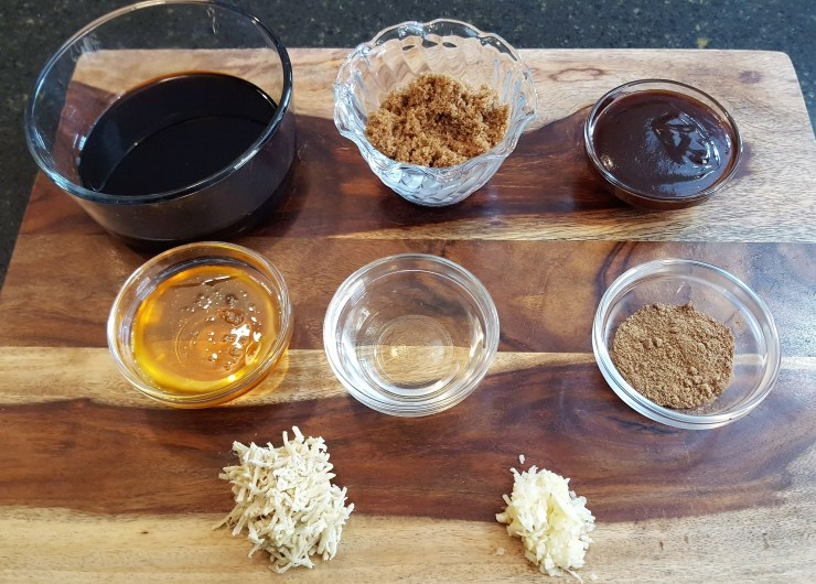A wooden cutting board with multiple bowls filled with soy sauce, brown sugar, hoisin sauce, honey, rice wine vinegar garlic and ginger