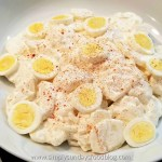 Bowl of potato salad topped with sliced hard cooked eggs and sprinkled with paprika