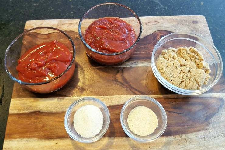 On a cutting board there are bowls containing 1 cup of ketchup, 1 cup of chili sauce, 1 cup of brown sugar, 1 tablespoon of garlic powder and 1 tablespoon of onion powder
