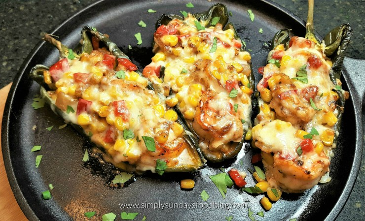 Green roasted poblano peppers stuffed with corn, red bell peppers, shrimp and creamy cheese served on a black cast iron flat pan