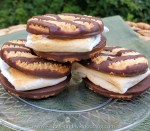 Three fudge striped smores stacked on top of each other on a plate