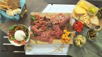 Charcuterie & Cheese Board with prosciutto, salami, sopressata, a basket of crackers, a bowl with burrata and tomatoes. A small cutting board with a chunk of parmesan, marinated olives and artichokes along with roasted red peppers and pickled cornichons