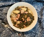 A white bowl on a blue and white cloth filled with smoked turkey, collard greens, potatoes, stock sprinkled with some crushed red pepper flakes