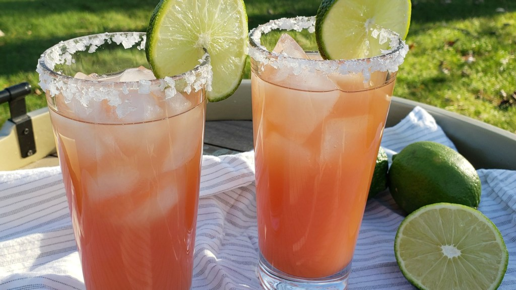 Two cocktail glasses with grapefruit, a salted rim, lime wheels for garnish and fresh limes in the background