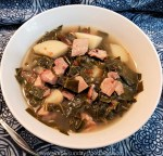 A white bowl of turkey and collard green soup on a blue cloth