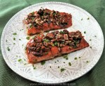 Oven roasted salmon glazed with maple syrup and honey giving it rich reddish brown color topped with toasted pecans and sprinkled with green fresh chives on a white textured plate