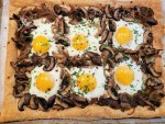 Puff pastry crust with caramelized mushrooms and onions which create six pockets that each hold an egg sprinkled with fresh green parsley, red pepper flakes and white shredded parmesan cheese