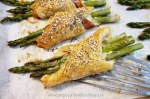 Roasted asparagus, salty prosciutto & creamy mozzarella wrapped in a light and flaky puff pastry on a baking sheet
