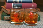 Two Manhattan cocktails with cherries on a cloth with stacked books in the background