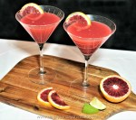 Two blood orange martinis on a board garnished with fresh blood oranges and limes