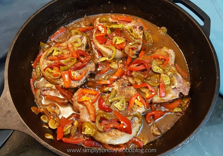 Seared and browned pork chops in a black cast iron pan covered with red, green peppers in a rich brown sauce