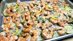 A sheet pan of shrimp in a garlic butter sauce with lemon & fresh herbs