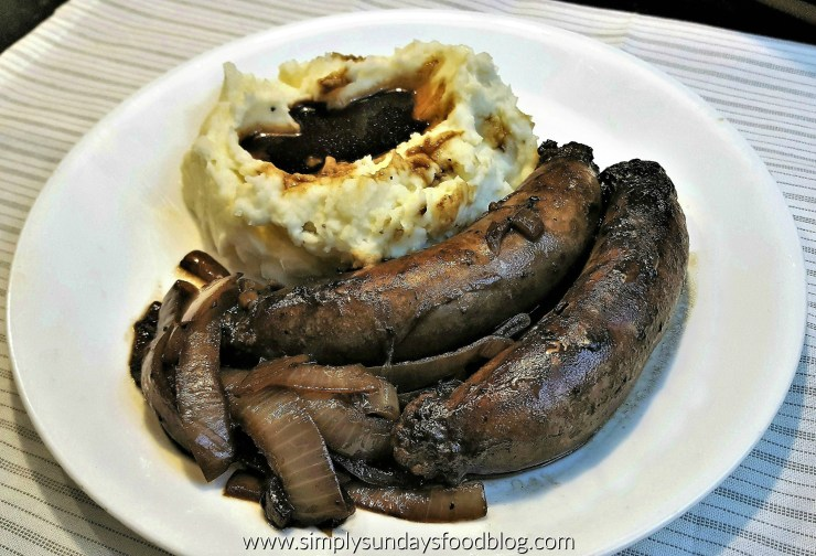Seared brown sausage braised in a rich brown onion gravy with a white creamy side of mashed potatoes topped with a rich brown gravy on a white plate