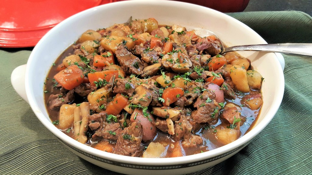 A hearty bowl of Lamb stew with vegetables sprinkled with chopped fresh parsley on a green cloth