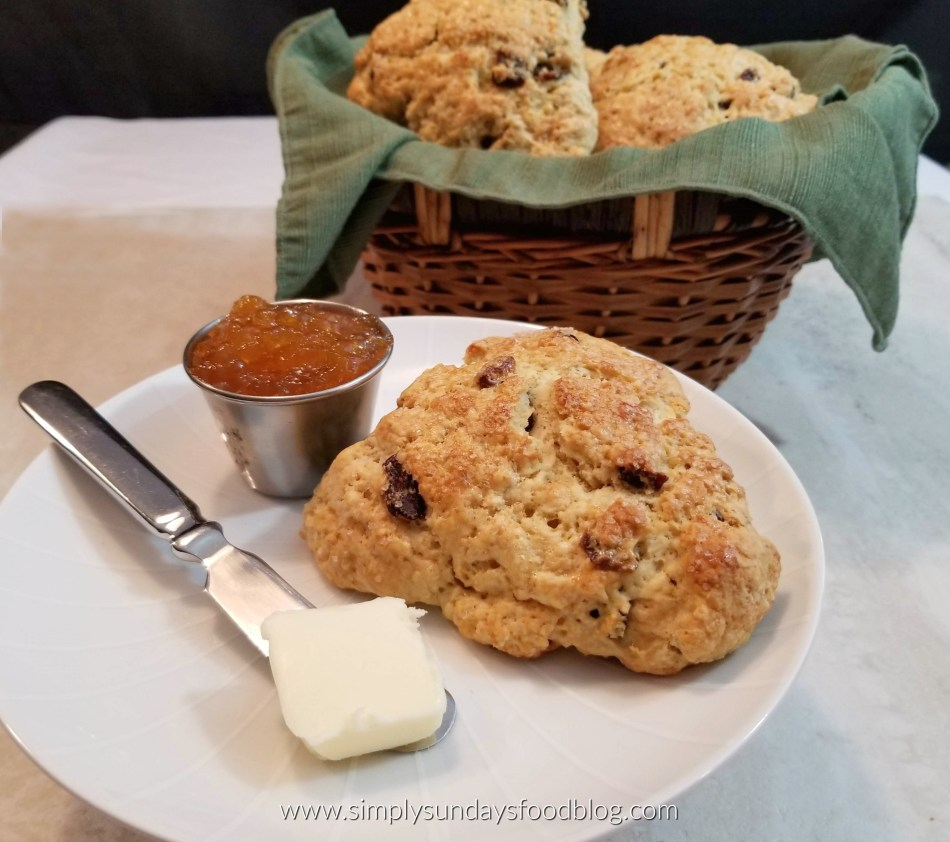 A small white plate with an Irish Soda Bread Scone, a spreader with a pat of butter and apricot jam. Basket lined with a green cloth filled with scones in the background