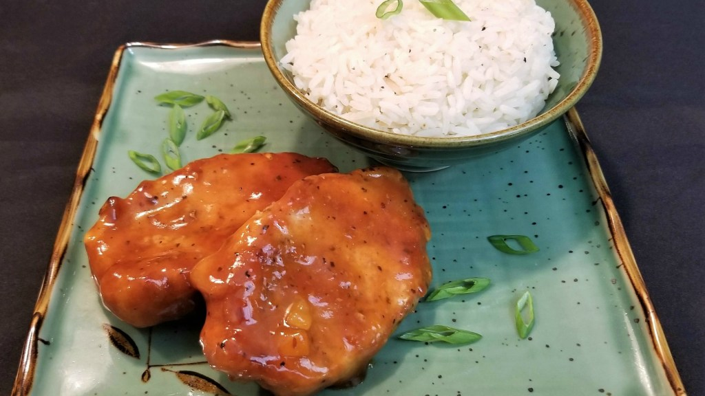 Two boneless pork chops smothered in a duck sauce glaze on a green oriental square plate garnished with scallions and served with a bowl of white rice